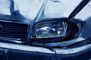 Blue car with dents and smashed headlight